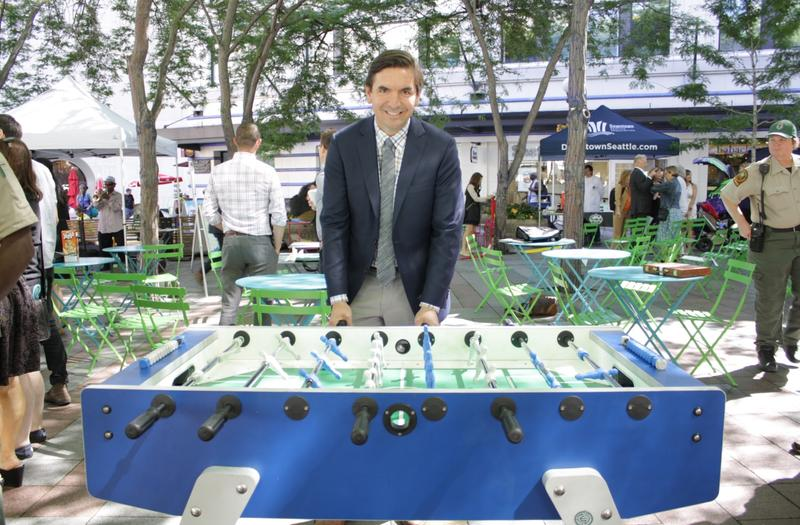 Joshua Curtis stands behind a foosball table.