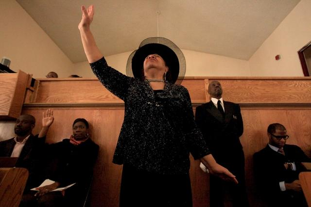 Maxine Dillon Holmes, center, raises her hands during the First African Methodist Episcopal Church's 125th year anniversary service Sunday, Nov. 20, 2011 in Seattle.