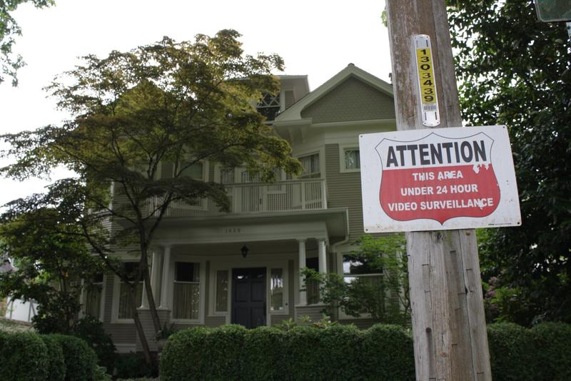 A sign in front of this large house warns of 24 hour video surveillance.