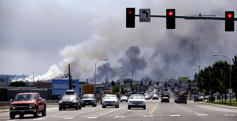 Smoke from several warehouses on fire, thought to have been sparked by embers from a wildfire that hit homes on a nearby hillside, fills the sky Monday, June 29, 2015, in Wenatchee, Wash.