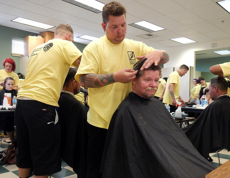 Homeless Army veteran Marvin Stanfield gets a free haircut from Adam Nolin of the Paroba College of Cosmetology.