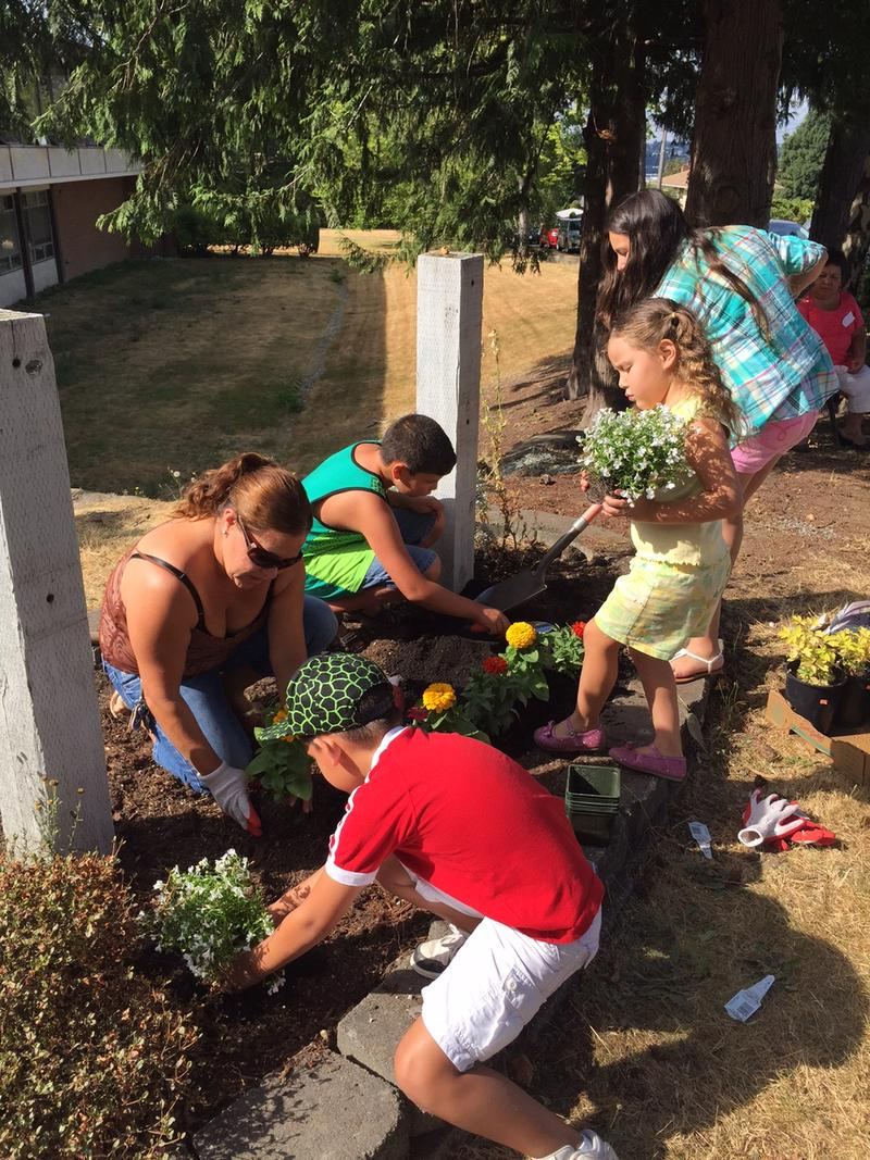 Arlene Nunez, left, and her family plant flowers outside Rainier Prep, which her 10-year-old daughter and 12-year-old son will attend this fall.