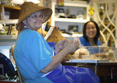 Artist Lois Thadei in woven hat, photographed at Ginger Street in Olympia during Art Walk.