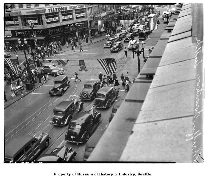 As Seattle grew, the downtown area became more crowded and busy. This August 1941 photo shows cars, buses and pedestrians at the intersection of Fourth Avenue and Pike Street.
