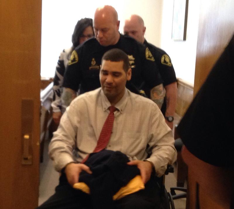 Guards wheel Monfort from the courtroom on Wednesday. Monfort is paralyzed from the waist down.