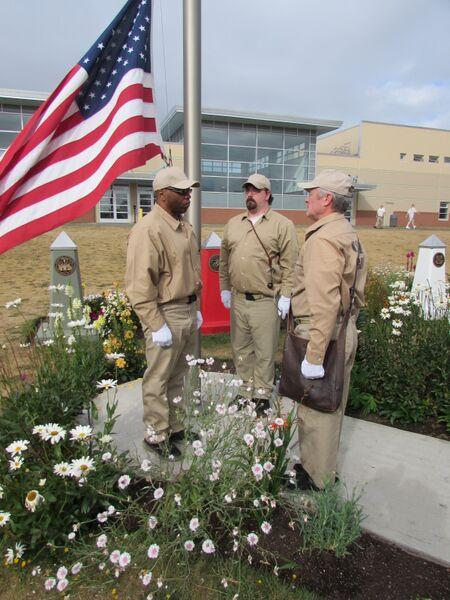 Derron Alexus (back to flag), James Bell (facing flag), Chadwick Kallebaugh (in between facing each other) raise the flag at  Stafford Creek Corrections Center in Aberdeen, Washington.