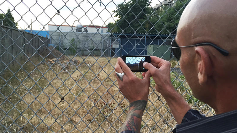 A Ballard man snaps a photo Monday night after a public meeting, as he mourns the loss of a tree, cut down recently by the city of Seattle.  The tree was on a vacant lot that may one day host a tent city for the homeless.