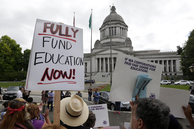 Demonstrators stand on the steps of the Temple of Justice and in view of the Legislative Building as they advocate for more state spending on education prior to a hearing before the state Supreme Court on Sept. 3, 2014, in Olympia.