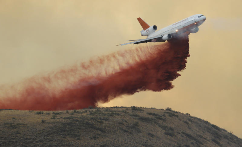 An air tanker drops red fire retardant on a wildfire near Twisp, Wash., Wednesday, Aug. 19, 2015.