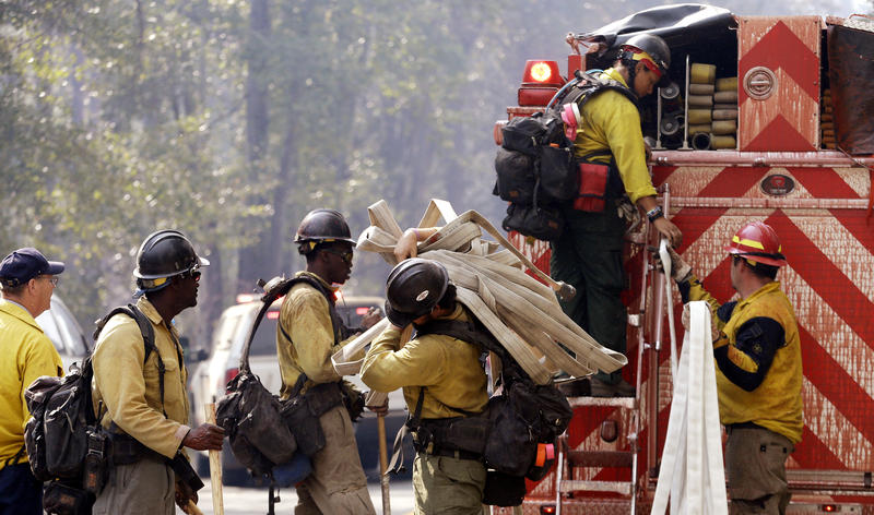 Firefighters line up to get gear out of the back of a fire truck as they get ready to head for a fire Thursday, Aug. 20, 2015, in Twisp, Wash.