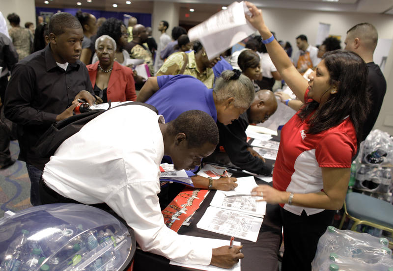 People apply for jobs at Coca-Cola at a jobs fair hosted by the Congressional Black Caucus in Miami, Tuesday, Aug. 23, 2011.