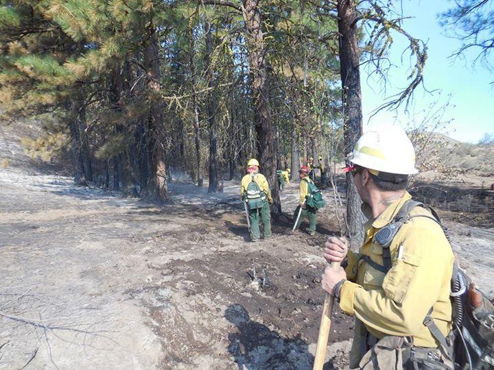 Firefighters from Salem, Oregon, mop up hotspots on Judy Doran McBride's ranch near Twisp this weekend.
