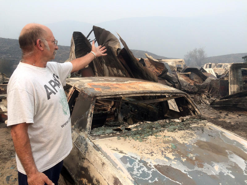 Steve Surgeon surveys the ruins after he lost outbuildings and vehicles in a wildfire on the outskirts of Okanogan, Wash., Sunday, Aug. 23, 2015. His home was saved , though.