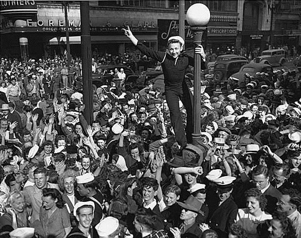 Sailor climbing a lamppost on V-J Day in Seattle, August 14, 1945.