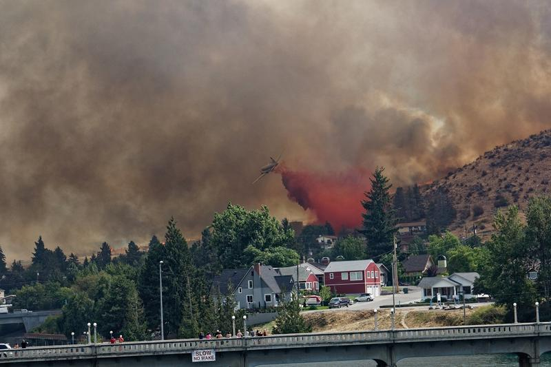 A plane dumps fire retardant on a ballooning wildfire on Aug. 14.