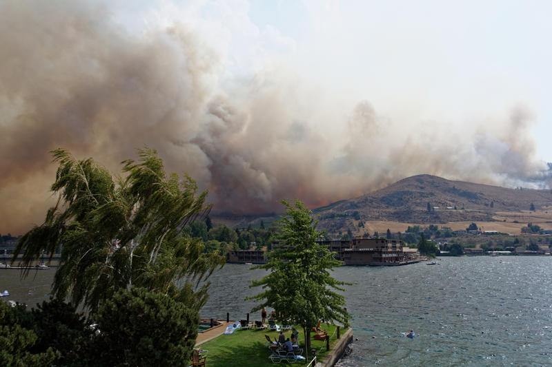 Beachgoers in Chelan watch as the wildfire comes over the butte.