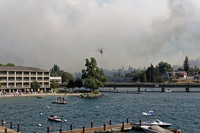 A helicopter moves toward Lake Chelan to pull up water to dump on wildfires. The wildfires started on the morning of Aug. 14; vacationers remained and watched the fire effort.