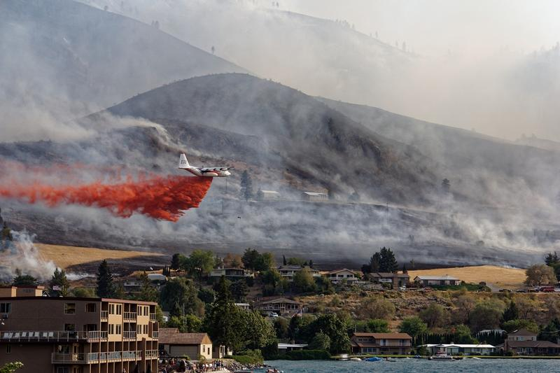 A DC-10 flies over Chelan within hours of a wildfire starting on Aug. 14. Sunbathers on holiday watched as the fire effort took hold.