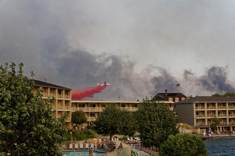A DC-10 dumps fire retardant on an approaching fire in Chelan, Washington. Vacationers at the Campbell's Resort watched as the firefighting effort took hold.