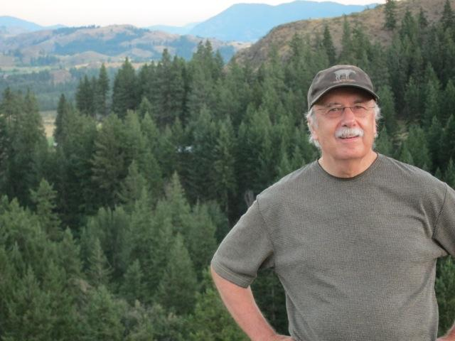 Don Nelson, the editor-owner of the Methow Valley News, with the Methow Valley in the background. The fires this season are the biggest on record in Washington state.