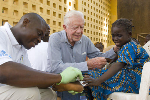 Former U.S. President Jimmy Carter comforts Ruhama Issah, 6, in Savelugu, Ghana, on Feb. 8, 2007, as Adams Bawa, a Carter Center technical assistant, tends her Guinea worm wound.