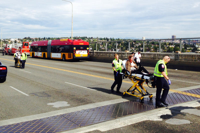 An injured person is taken from the scene of the Aurora Bridge bus crash on Thursday.