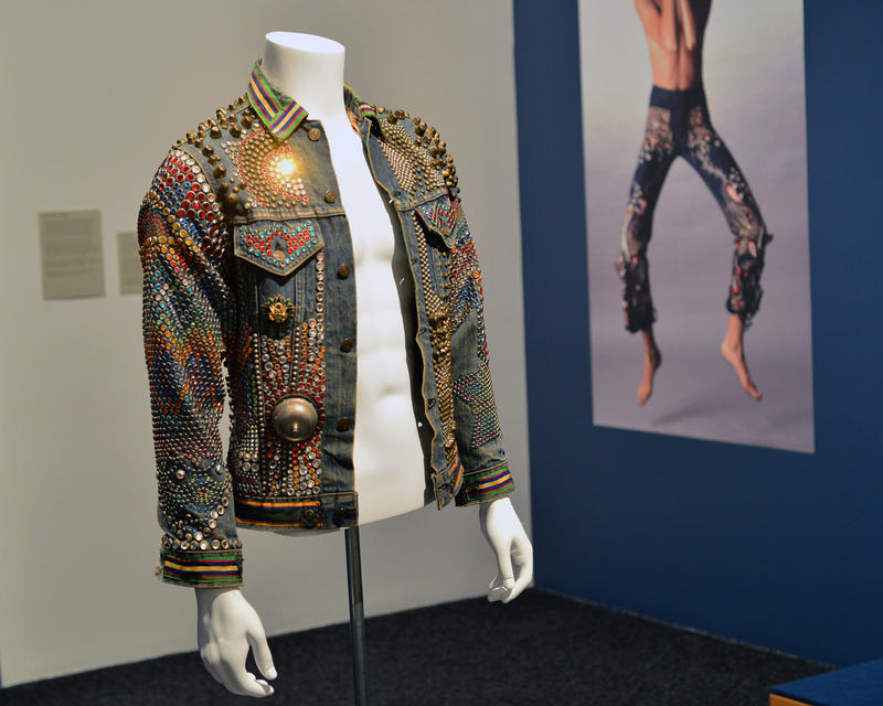 """Welfare,"" by Billy Shire. This denim jacket has metal studs, crystal beads and a call bell on the back. The jacket won the 1974 Levis Denim Art contest. In the background, a photo by Sam Haskins."