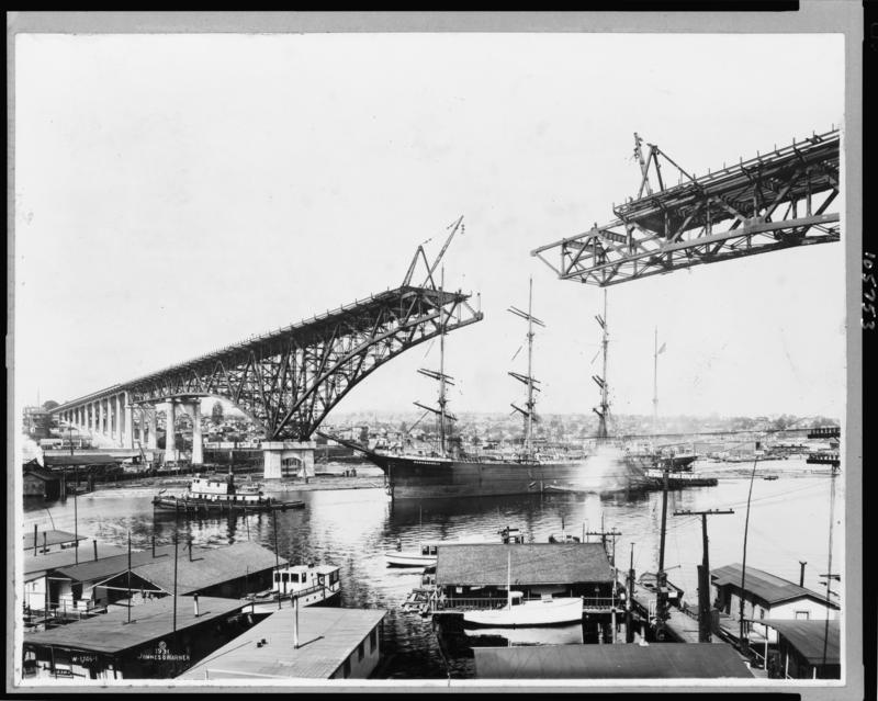 The tall ship Monogahela passes under the uncompleted Aurora Bridge circa 1931.