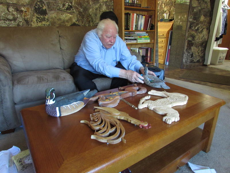 Henry Chamberlain shows some of the wood carvings that he makes, even at age 93.