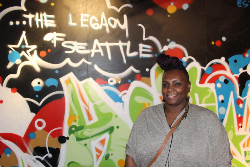 Jazmyn Scott stands in front of a mural created for MOHAI by SPECSWIZARD who has been making art and beats in Seattle since 1978.