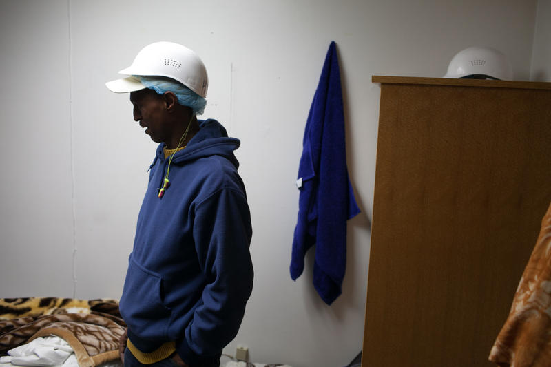 Abdirahman Shire in his dormitory room. Room and board are free or cost less than $15 a day for seafood processing workers (depending on their contract and from plant to plant).