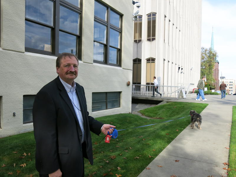 Dave Somers walks Hewitt the dog outside the existing county courthouse.