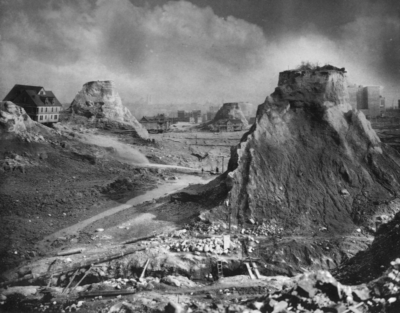 """Spite Mounds,"" 1910. The most famous image of the Denny Regrade is often described as depicting ""spite mounds."" But writer David Williams says, at least in one case, it wasn't spite at all that kept these mounds standing. Just paperwork."