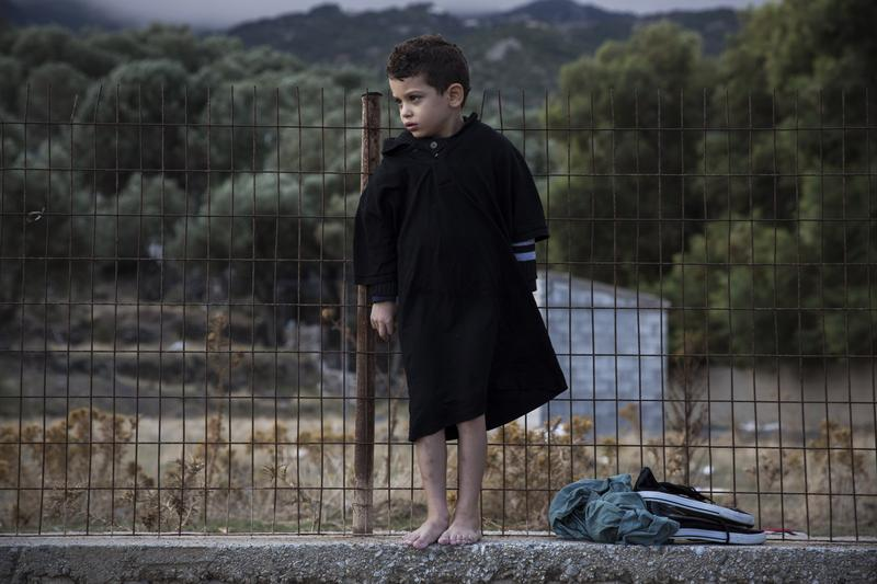 A barefoot boy stands on a cement wall after his family's arrival on a dinghy from the Turkish coasts to the northeastern Greek island of Lesbos. About half a million refugees have crossed the Mediterranean this year, although few will end up in Seattle.