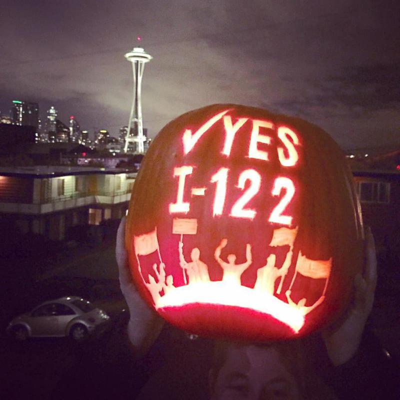 A supporter of Initiative 122 displays a carved pumpkin.
