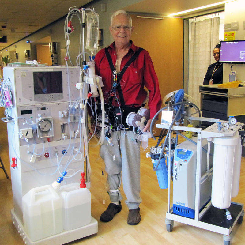 Chuck Lee, wearing the Wearable Artificial Kidney, happily stands in contrast to two less-portable dialysis options.