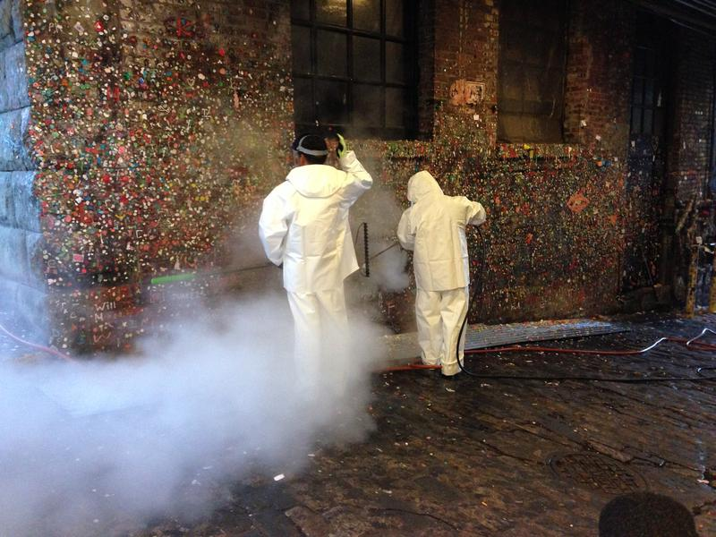Workers using steam cleaners to blast the gum off the walls of Post Alley below Pike Place Market on Tuesday, Nov. 10, 2015.