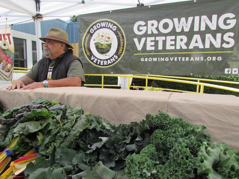A veteran who goes by Cheech One-Road works Growing Veterans farm stand at the VA Hospital in Seattle.