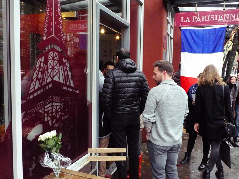 People gather Saturday at La Parisienne bakery in Seattle's Belltown to show support after the terrorist attacks in Paris.