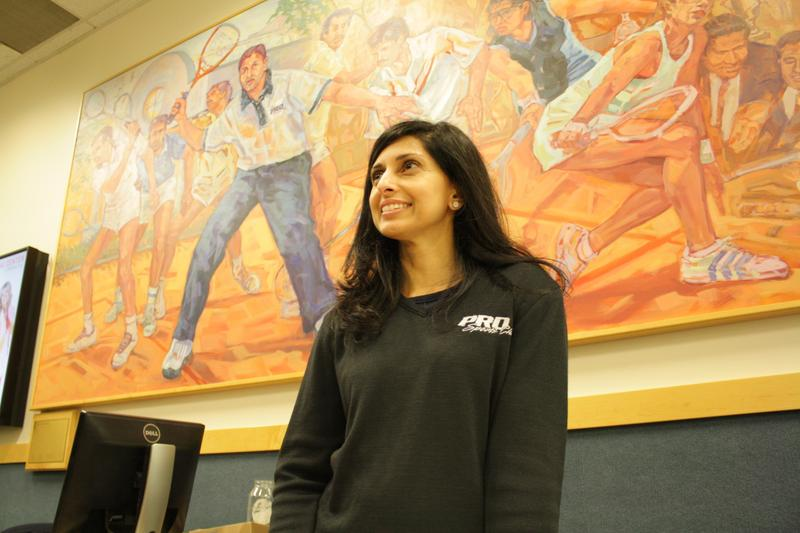 Shabana Khan stands in front of a painting at Pro Sports, Bellevue, that depicts members of her family playing squash. (Shabana is the one in blue, while her brother Azam is in the center of the painting at her left).