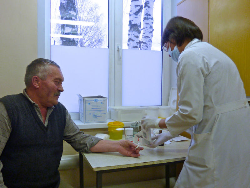 A doctor takes a blood sample from an older patient.
