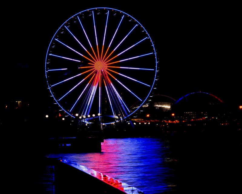 The French flag's blue, white and red light the Seattle Great Wheel and are reflected in Elliott Bay on Saturday night.