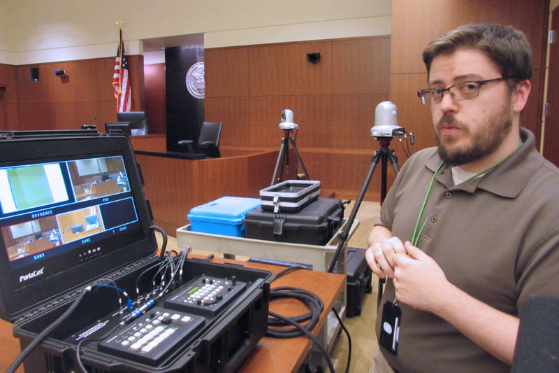 Courtroom technology administrator Jeremy Sites explains the camera setup in U.S. District Court.