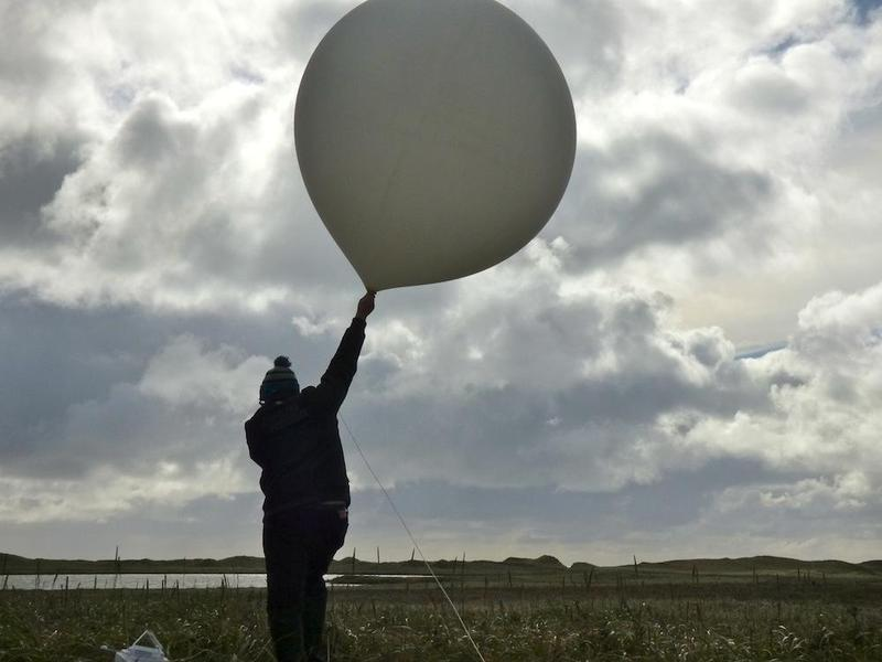 William Wells raises a weather balloon for launch on St. Paul Island, Alaska.