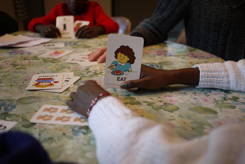 Several refugee children gather around the table for a playful English lesson. Whoever shouts out the correct word on the flashcard, keeps it.