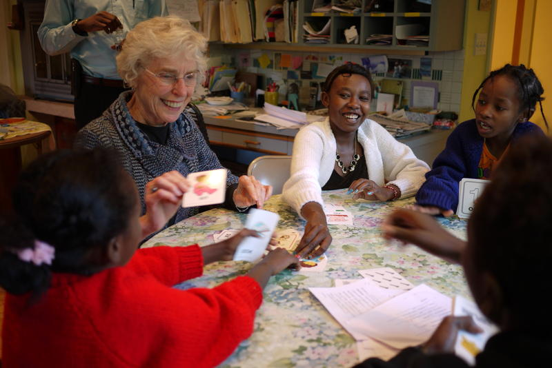 Host Carlene Kennedy, center, uses flashcards to help her refugee guests learn English. Kennedy has hosted refugees in her home since 1975.