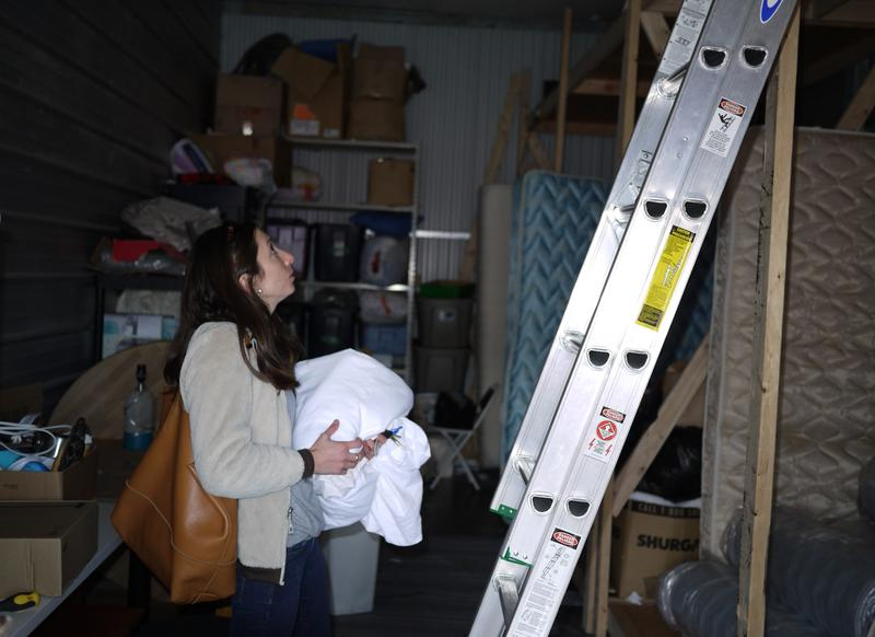 Cordelia Revells, resettlement manager with Jewish Family Service, sorts through furniture donations for new refugees.