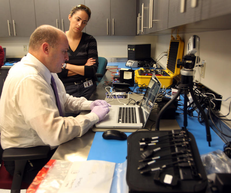 In this photo taken Wednesday, Sept. 18, 2013, Sgt. Rick Nelson works on locating information on a hard drive with Det. Caitlin Rebe at the Internet Crimes Against Children unit in Manchester, N.H.