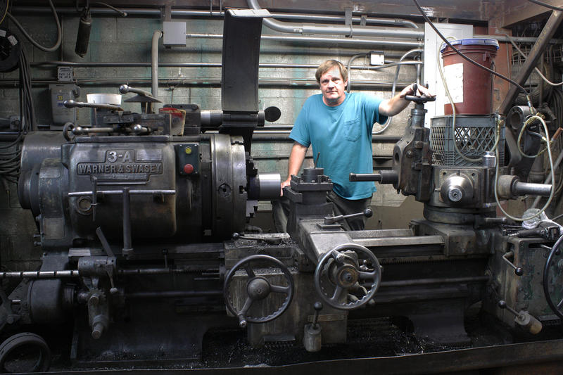 Metal fabricator Denny Jensen with a metal lathe, one of the many old machines he restored and uses at the old Fenpro building in Ballard.