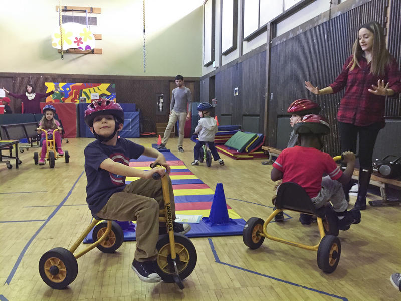 Kindergarteners take turns on the tricycles at the EEU gym class.